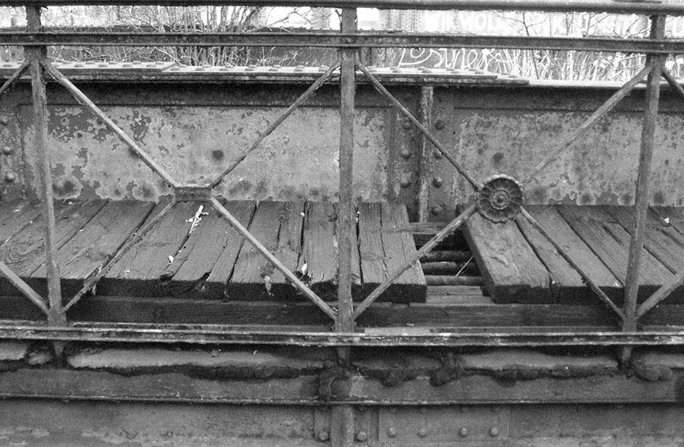 Laufsteg und Geländer einer Brücke der Potsdamer Bahn: Jedes Geländerfeld ist miteiner Rosette verziert.